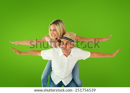 Happy man giving his partner a piggy back against green vignette - stock photo