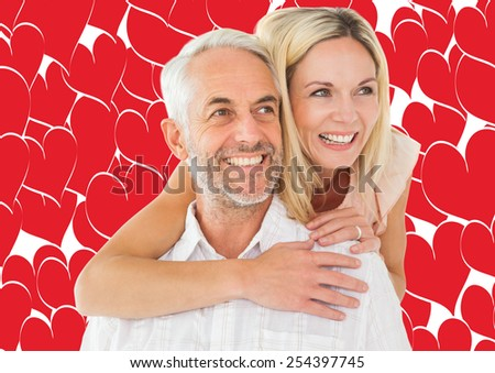 Happy man giving his partner a piggy back against valentines day pattern - stock photo