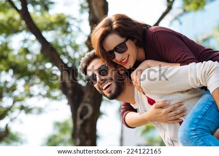 Happy man giving piggyback ride to his beautiful girlfriend - stock photo