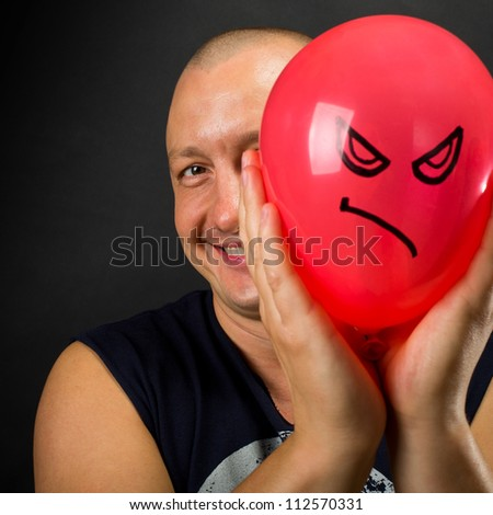 Happy man hiding behind red balloon with angry smiley - stock photo
