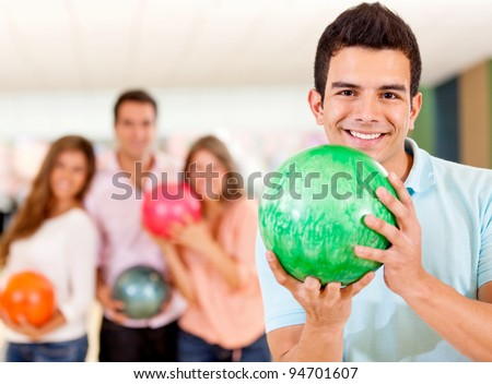 Happy man holding a bowling ball playing with friends