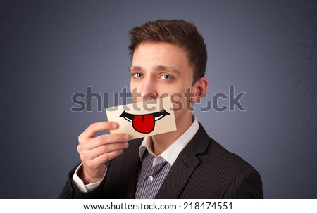 Happy man holding card with funny smiley on gradient background - stock photo