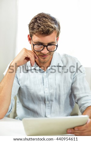 Happy man holding digital tablet in office - stock photo