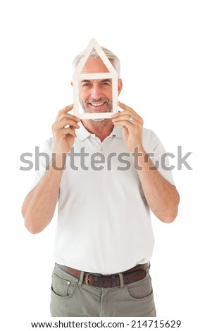 Happy man holding house outline over face on white background