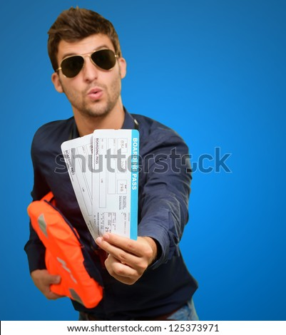 Happy Man Holding Life Jacket And Boarding Pass On Blue Background