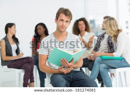 Happy man holding notebook while colleagues are talking behind him in creative office - stock photo
