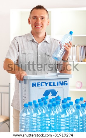 Happy man holding plastic bottle with recycling bin