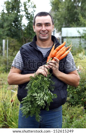 Happy man  holds a bunch of harvested carrots