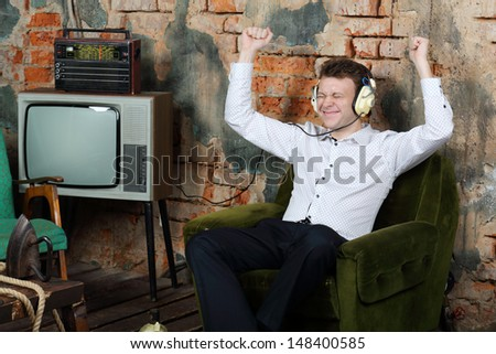 Happy man in big white headphones listens old radio and sits in armchair in very old house. - stock photo