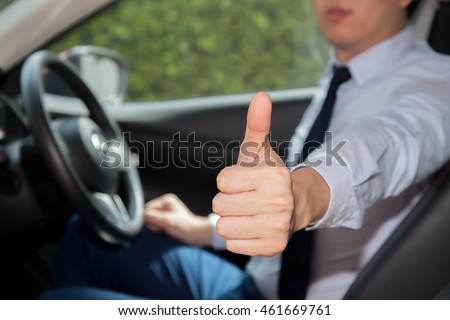 Happy man in casual suit giving thumbs up to someone in the car - indicates driving approval and confidence