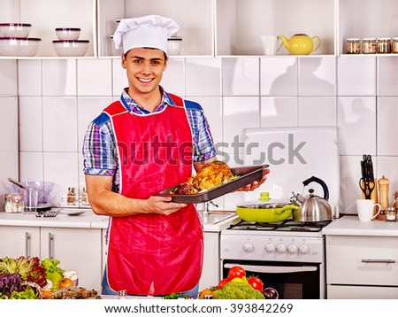 Happy man in chef hat cooking chicken. Cooking food. - stock photo