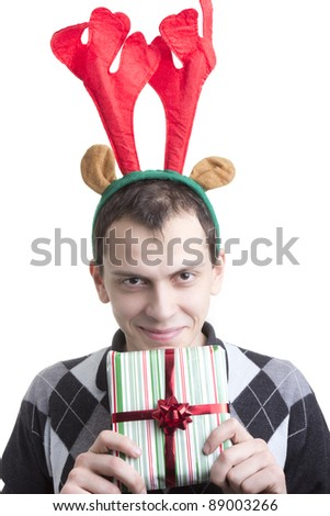 Happy man in Christmas party elk horns holding red gift box