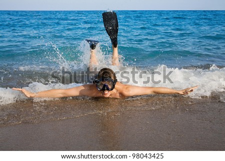 Happy man in goggles and flippers doing splashing in the red sea - stock photo