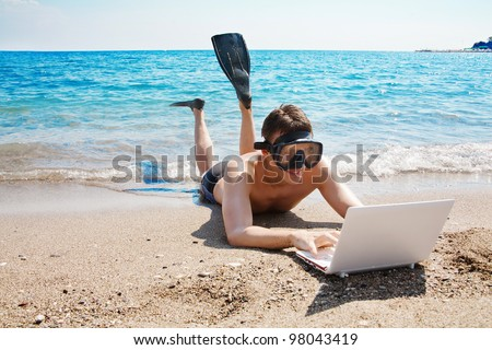 Happy man in goggles and flippers typing on the laptop at the beach - stock photo
