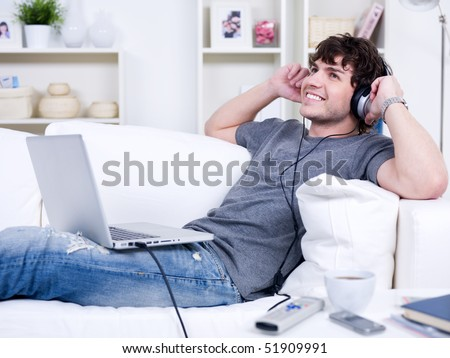 Happy man in headphones with laptop relaxing on the sofa at home