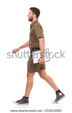Happy man in khaki uniform walking and carrying clipboard. Full length studio shot isolated on white. - stock photo