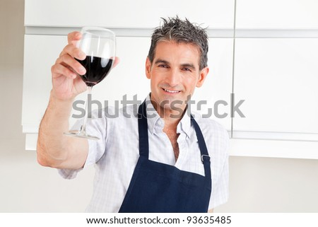 Happy man in kitchen drinking red wine and cheering - stock photo