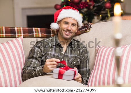 Happy man in santa hat opening a gift at home in the living room - stock photo