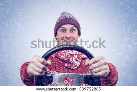 Happy Man in sweater and hat with a steering wheel, snow blizzard. Concept car driver.