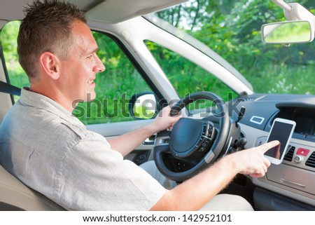 Happy man in the car using his mobile as a navigation GPS or receiving call - stock photo