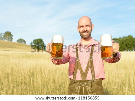 happy man in traditional bavarian garb with two mugs of beer - stock photo