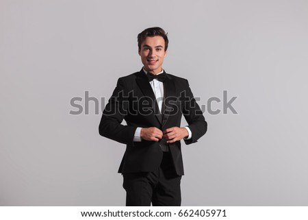happy man in tuxedo buttoning his coat on grey background