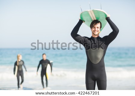 Happy man in wetsuit carrying surfboard over head on the beach - stock photo