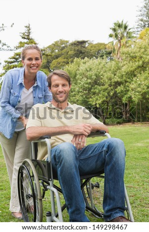 Happy man in wheelchair with partner smiling into the camera in the park
