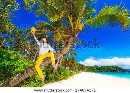 Happy man in yellow trousers and white shirt sitting on a palm tree on a tropical beach and a welcome waving yellow hat. Summer vacation concept . - stock photo