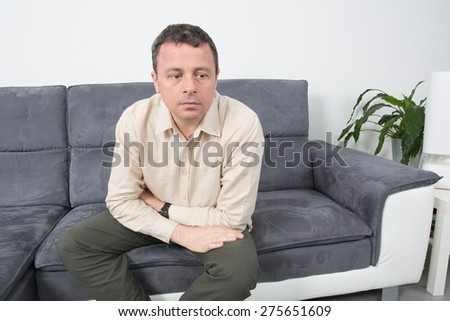 Happy  man is relaxing on sofa and looking at the camera