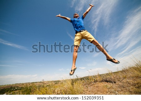 Happy man jumping, blue sky on background, wide angle - stock photo