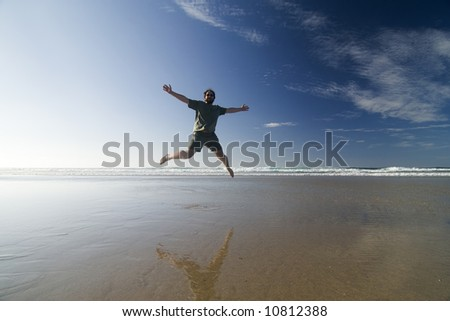 Happy man jumping in a sunny beach