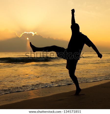 Happy man jumping over sea. Sand beach at dawn.