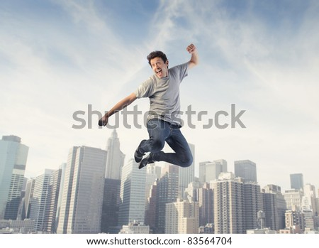 Happy man jumping with cityscape in the background - stock photo