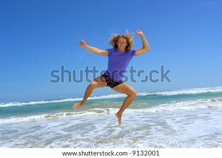Happy man jumps high on sea beach with splashes. Shot in Hermanus, Walker Bay, Western Cape, South Africa.