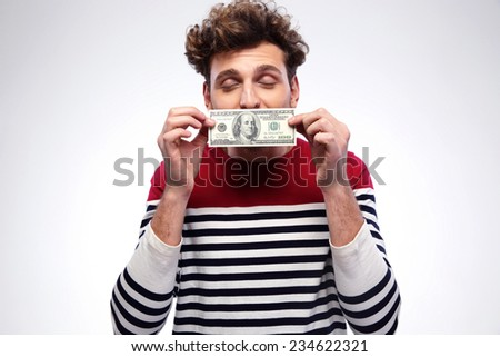 Happy man kissing dollar bill over gray background - stock photo