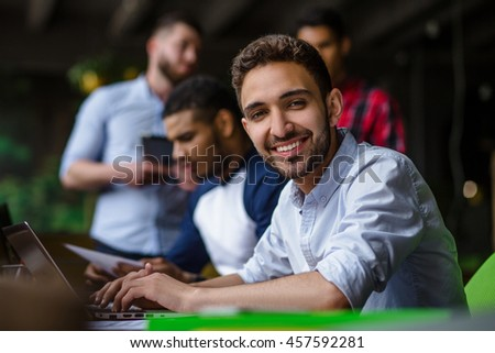 Happy man looking at camera and smiling. Handsome businessman working on laptop computer in modern office interior.