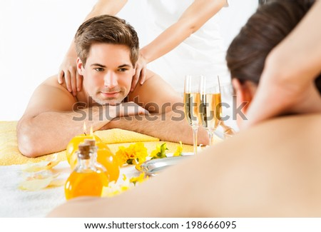 Happy man looking at woman while receiving shoulder massage in beauty spa