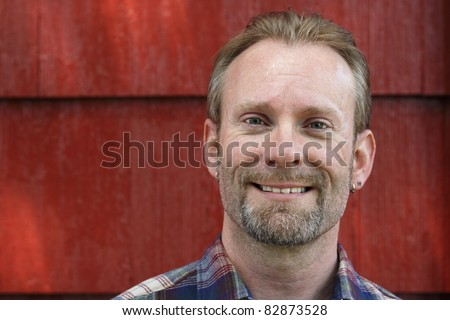 Happy man looking into the camera with a red house behind him in the day. - stock photo