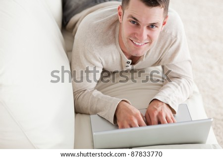 Happy man lying on a couch with a notebook in his living room - stock photo