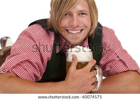 Happy man lying on floor holding oktoberfest beer stein. Isolated on white background. - stock photo