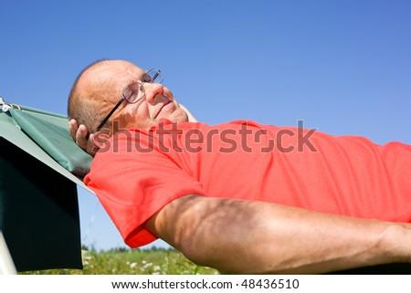 Happy man lying on hammock - stock photo