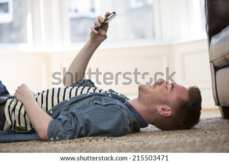 Happy man lying on the floor at home using his smartphone. - stock photo