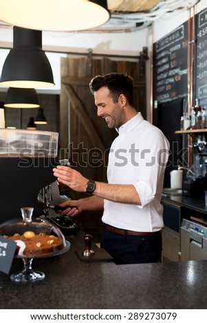 Happy man making coffee at restaurant - stock photo