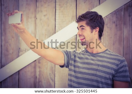 Happy man making face while taking selfie against wooden wall