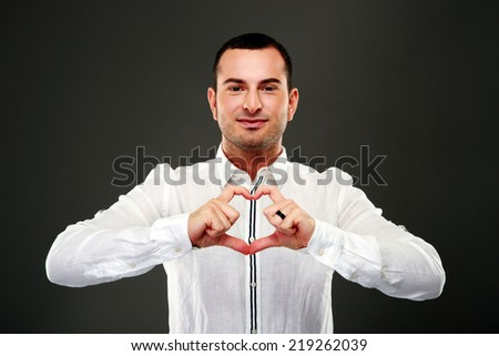 happy man making heart from his hands on black background - stock photo
