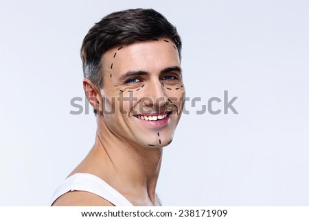 Happy man marked with lines for plastic surgery - stock photo