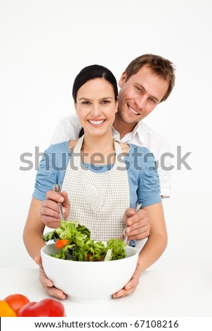 Happy man mixing a salad with his girlfriend in the kitchen at home - stock photo
