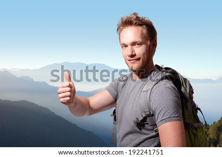 happy man mountain hiker with backpack and show thumb up on the top of mountains. caucasian