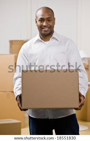 Happy man moving into new home carrying cardboard box